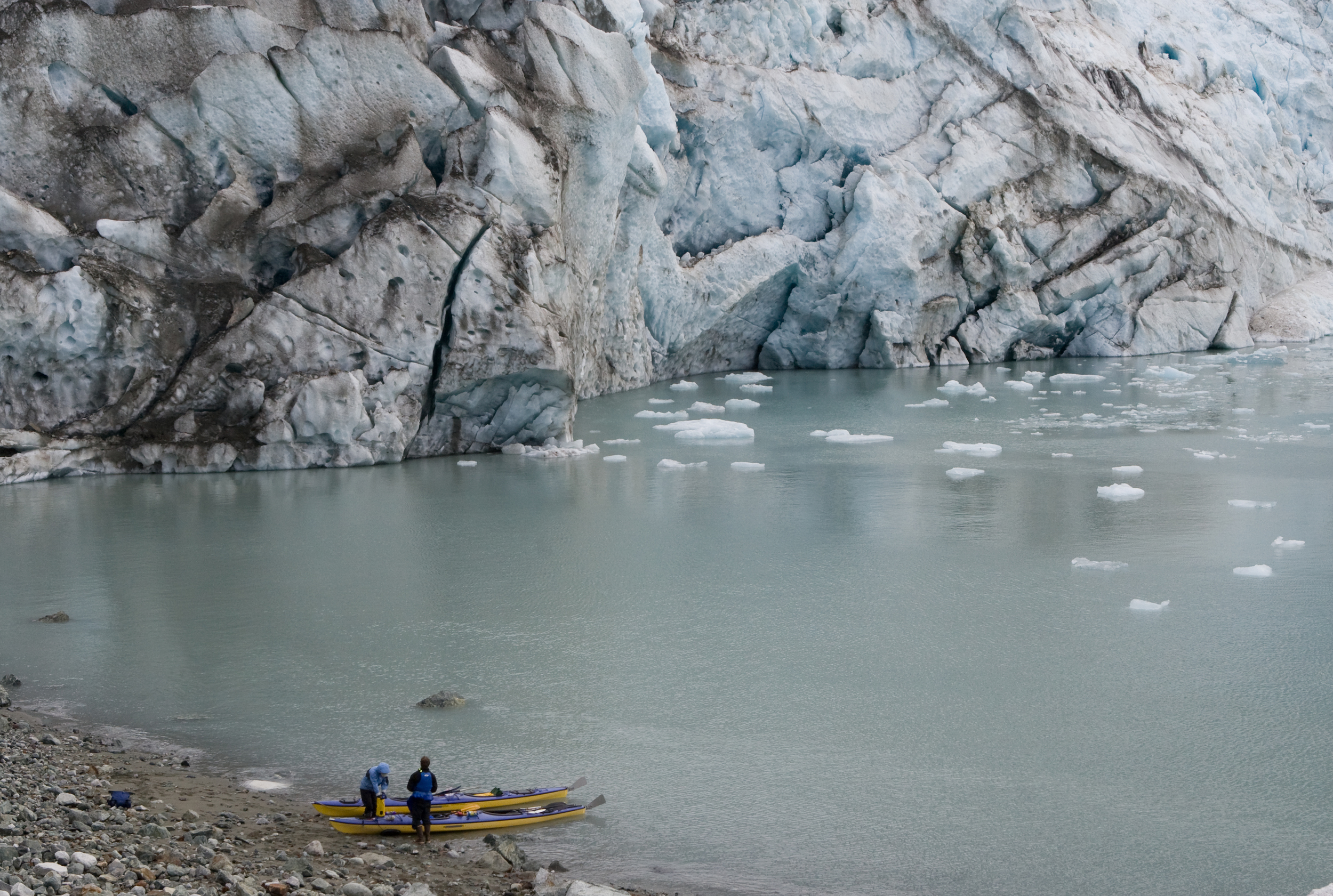 Paddlers land on the beach near Lamplugh Glacier while exploring Glacier Bay National Park by kayak.