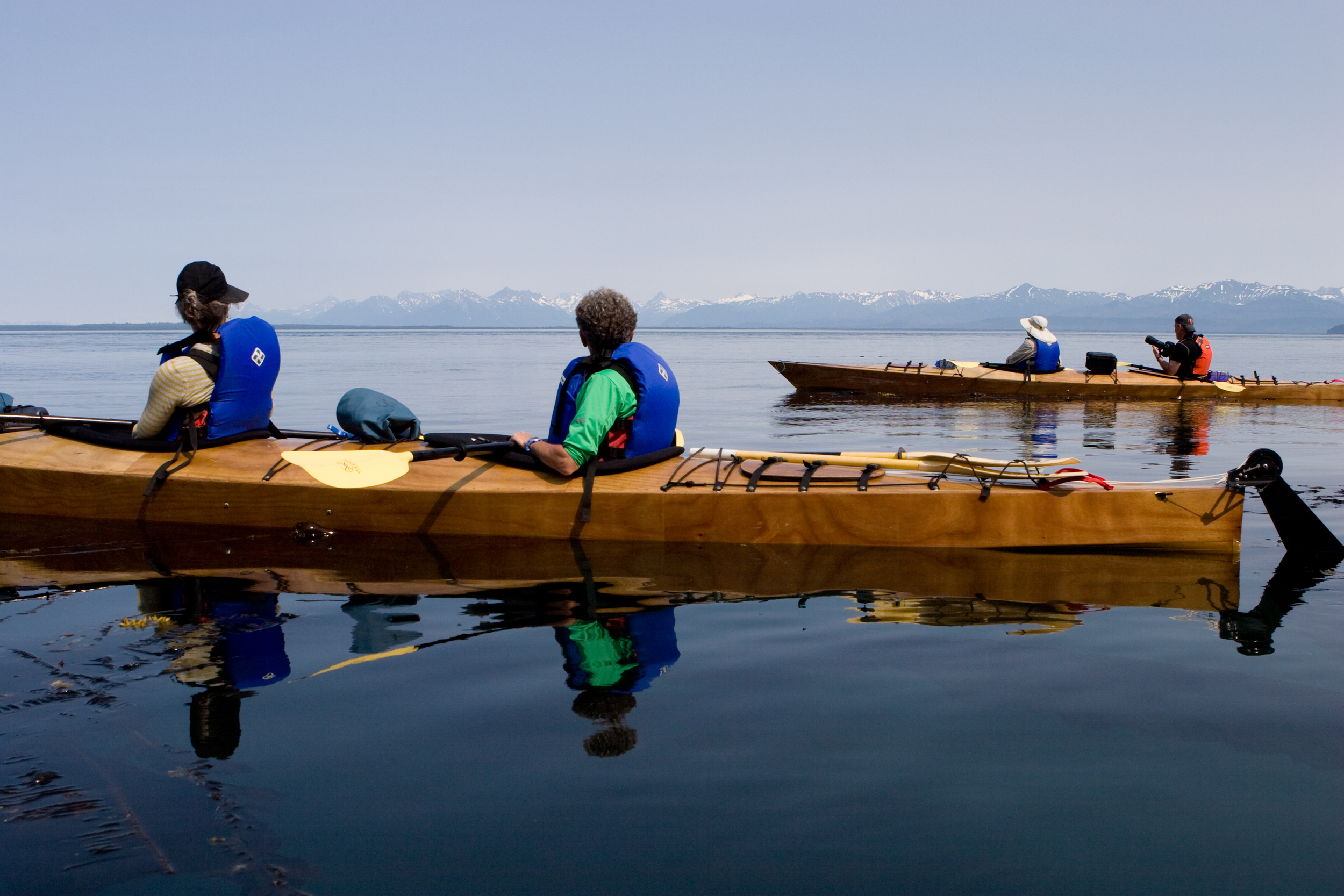 A group of kayakers watch the waters of Icy Strait for signs of humpback whales. Chichagof Island, Alaska.