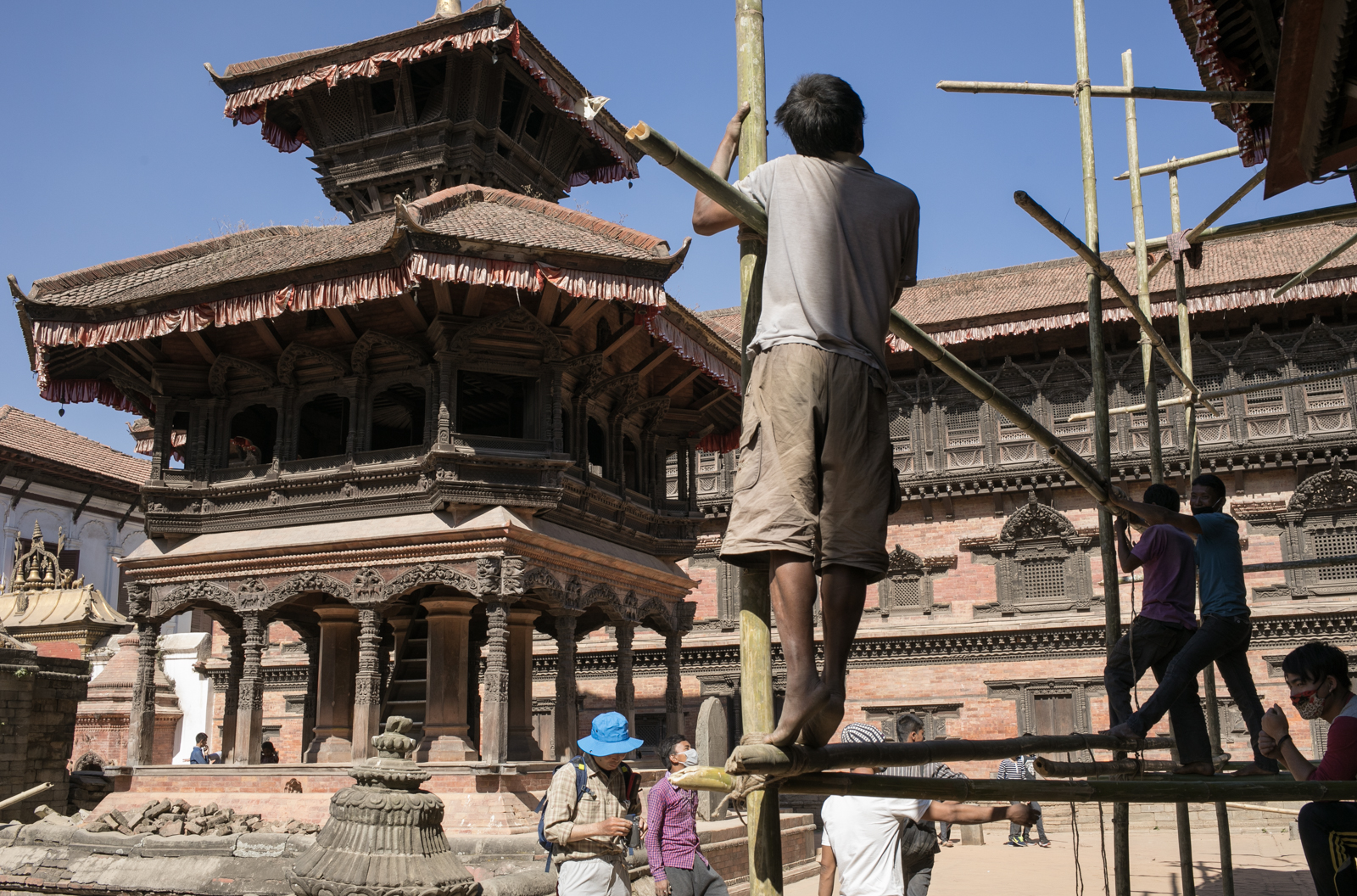 Men stand on temporary framework that was put into place for the reconstruction of the temples.