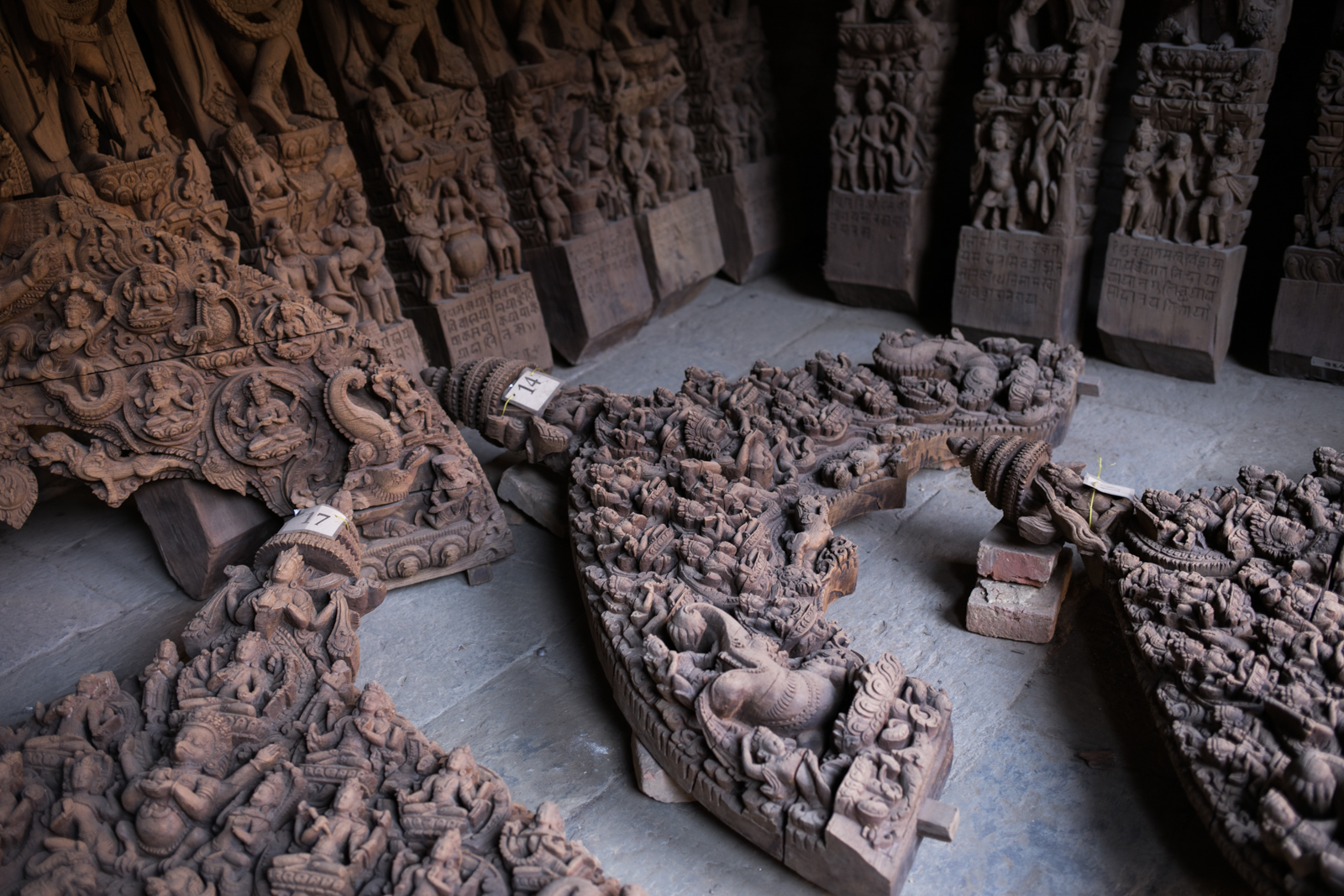 A collection of wooden carvings cataloged and stored until the structures they adorned are repaired.