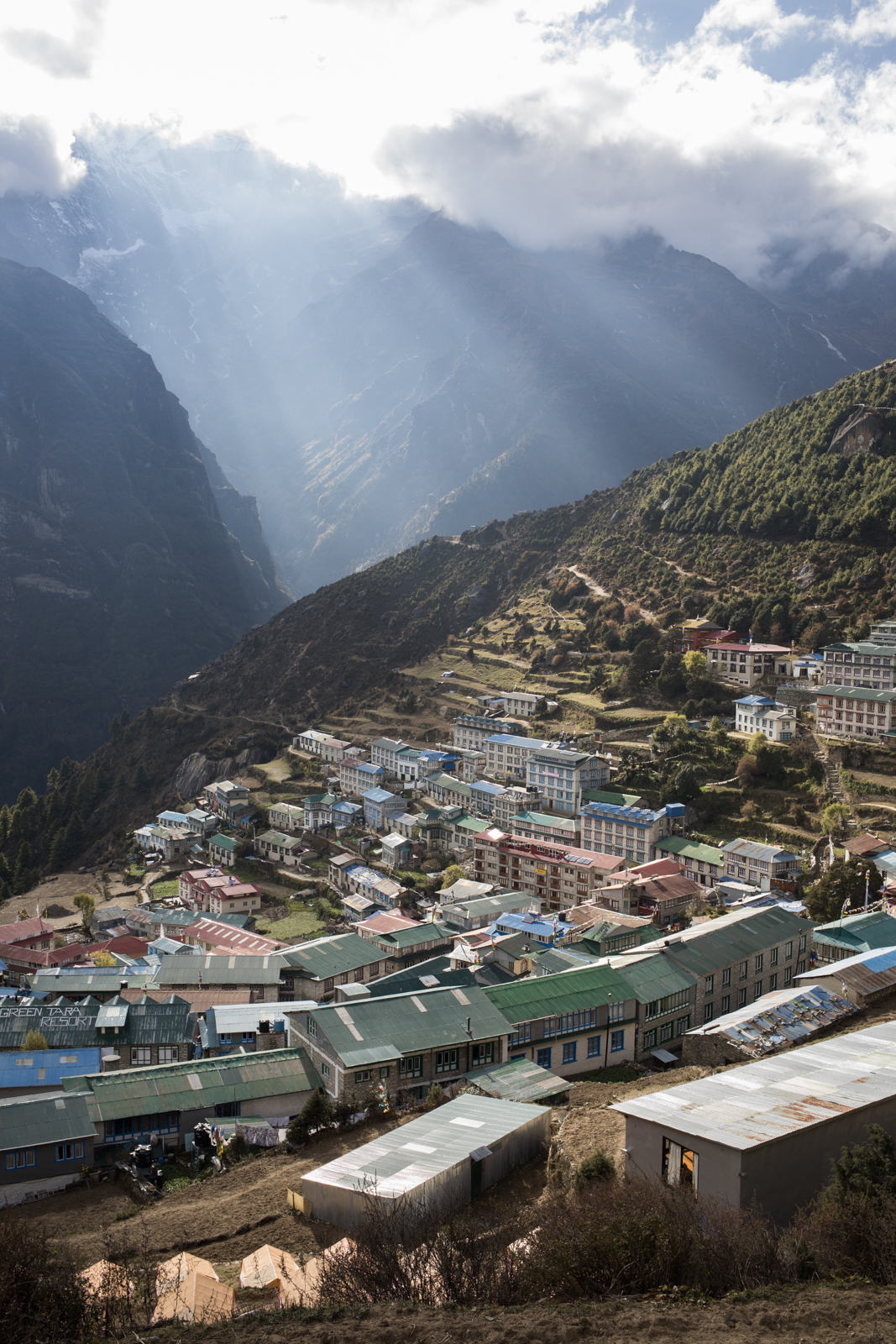 Clouds over Kangde Lho begin to break up as the evening light shines down on the village of Namche Baazar.