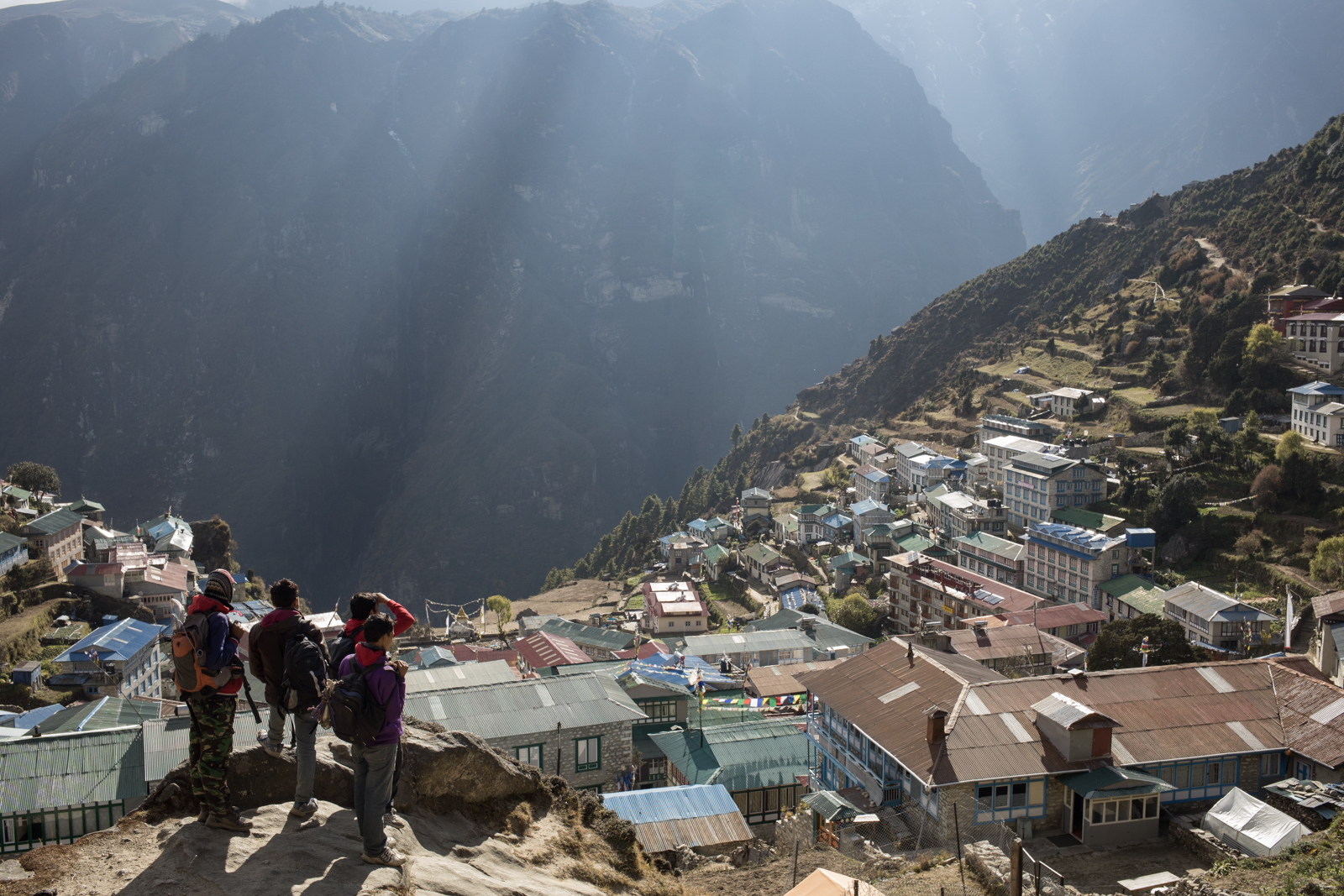 A group of young men look out over the village of Namche light breaks through the clouds.
