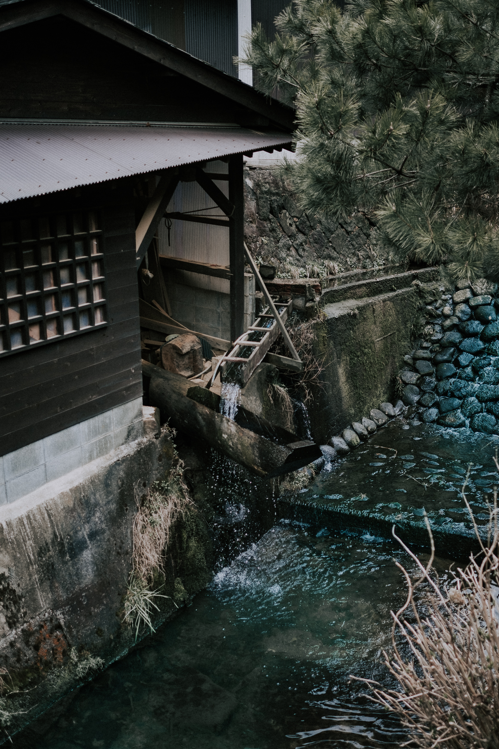 A karausu in Ontayaki no sato. As it fills with water the opposite side lifts up. When the water spills out, the other side drops and pounds the clay into powder.