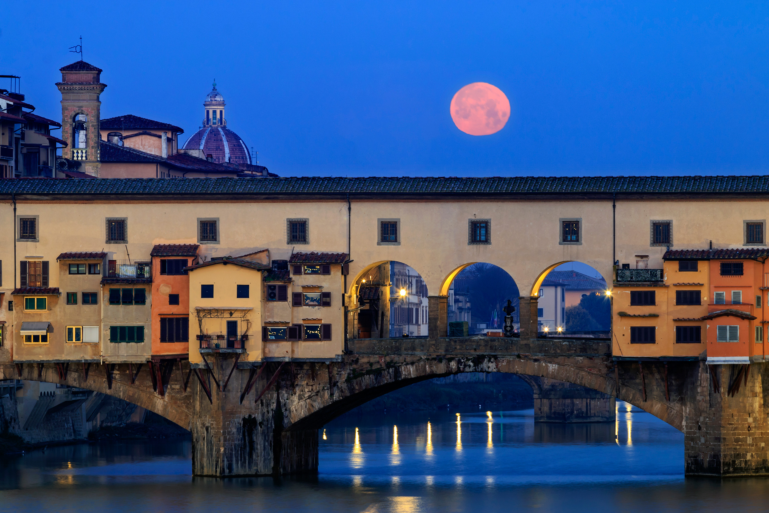 Sunrise from Ponte alle Grazie in Florence, Italy, with the full moon setting behind Ponte Vecchio