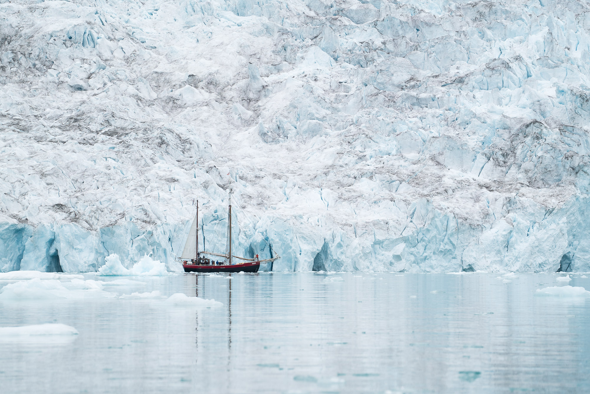 Expedition sailboat Aktika motoring past an unnamed glacier in Courtauld fjord, Kangerlussuaq, east Greenland.