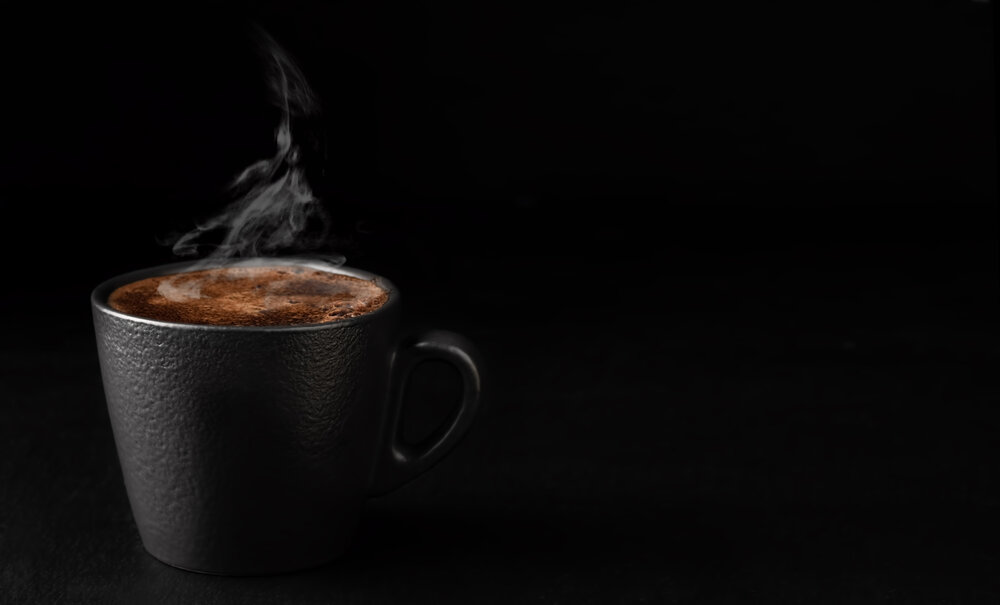 A wisp of steam against a dark background, and warm tones, leave no doubt this cup of coffee would be a satisfyingly hot sip.