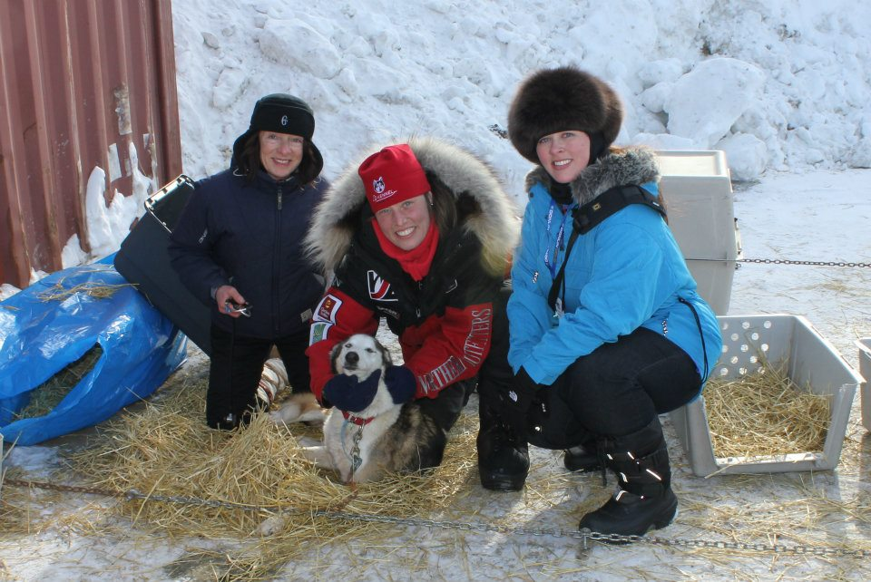 With Aliy Zirkle (center) who finished second in the 2012 Iditarod Trail Sled Dog Race. Here we are at the Nome Dog Lot when I was an official Iditarod volunteer. Her smile lights up a room.