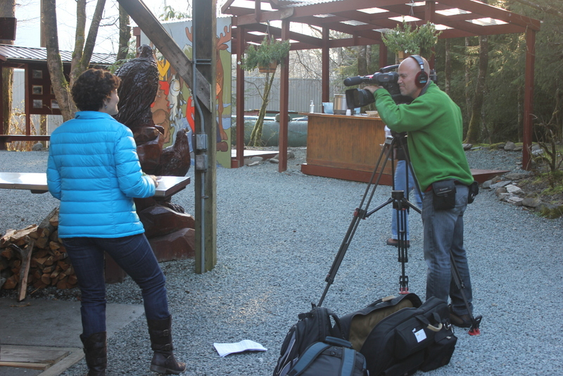 Meegan on camera, highlighting the delicious food at the Gold Creek Salmon Bake.