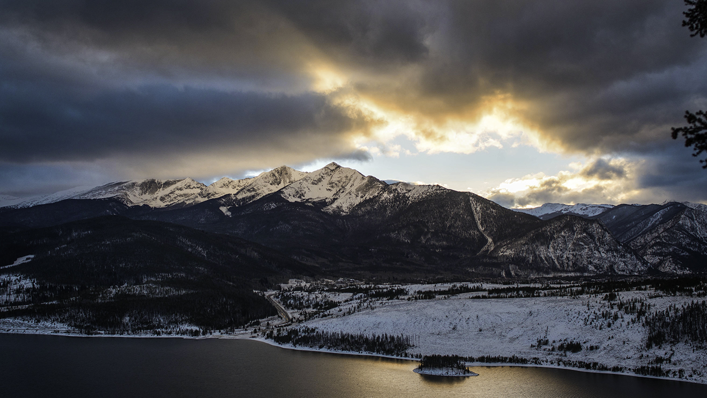View at sunset of Peak 1 and Tenmile Peak across the Blue River Arm of Dillon Reservoir, taken from Sapphire Point off Swan Mountain Road. U.S. Hwy 9 is visible along the shore of the reservoir.