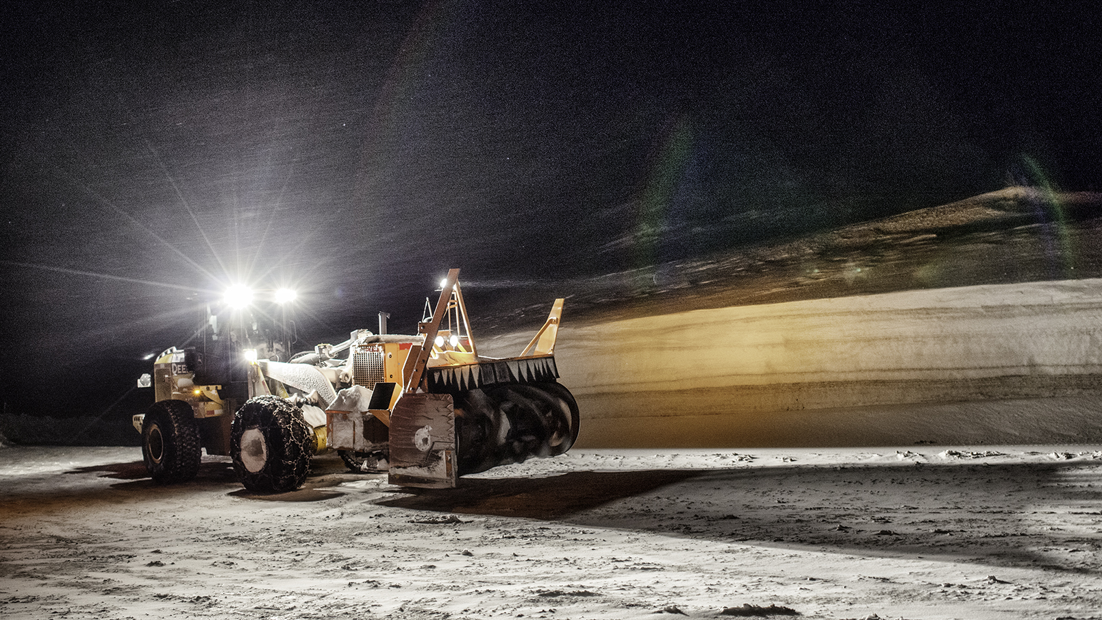 Snow removal equipment operates into the night on Loveland Pass. Notice the wall of snow on the other side of the road.