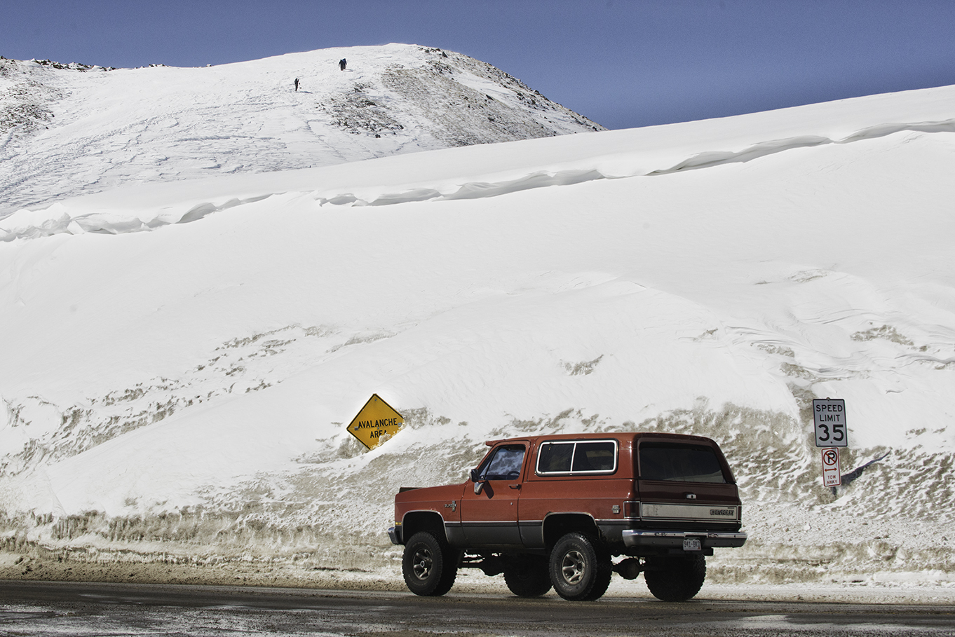 A Chevy Blazer crosses over the top of the pass in front of a buried Avalanche Area sign. Snowboarders can be seen up on the hill, hiking for a good spot to drop in.