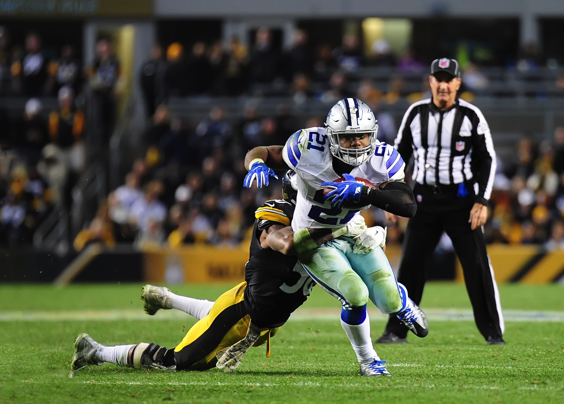 Ezekiel Elliott finishing a strong run against the Steelers defense.