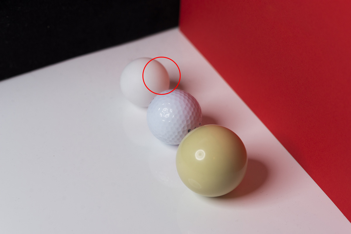 Take a look at how the white table tennis ball has been coloured pink due it's proximity to the red surface.