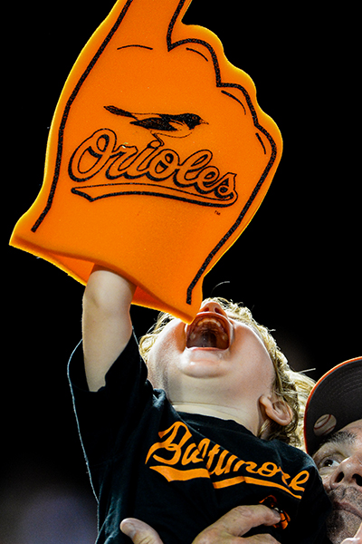 A young Orioles fan yells in excitement as his father lifts him up above his head.