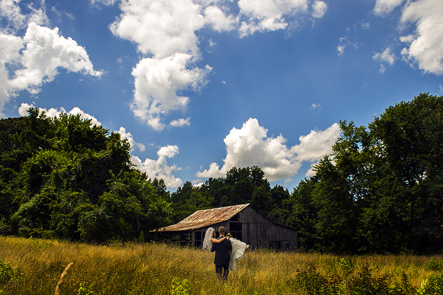 Evan Krenik carries his soon-to-be wife through a field on their wedding day in Huntingtown, Md.