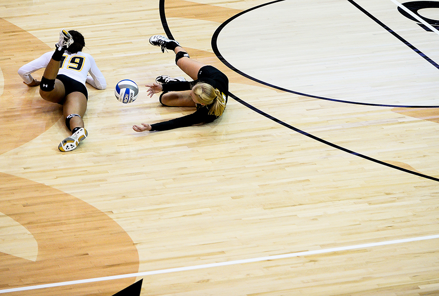 Towson University volleyball players attempt to dive for a ball during their home opener against Coppin State University in Baltimore, MD.