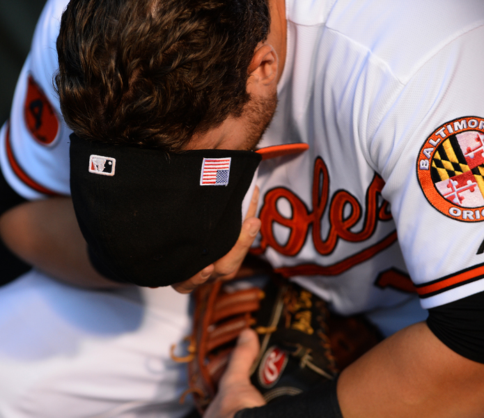 Baltimore Orioles first baseman Chris Davis removes his hat and covers his face in thought while preparing for a home game against the New York Yankees on Sept. 11, 2013 in Baltimore, Md.
