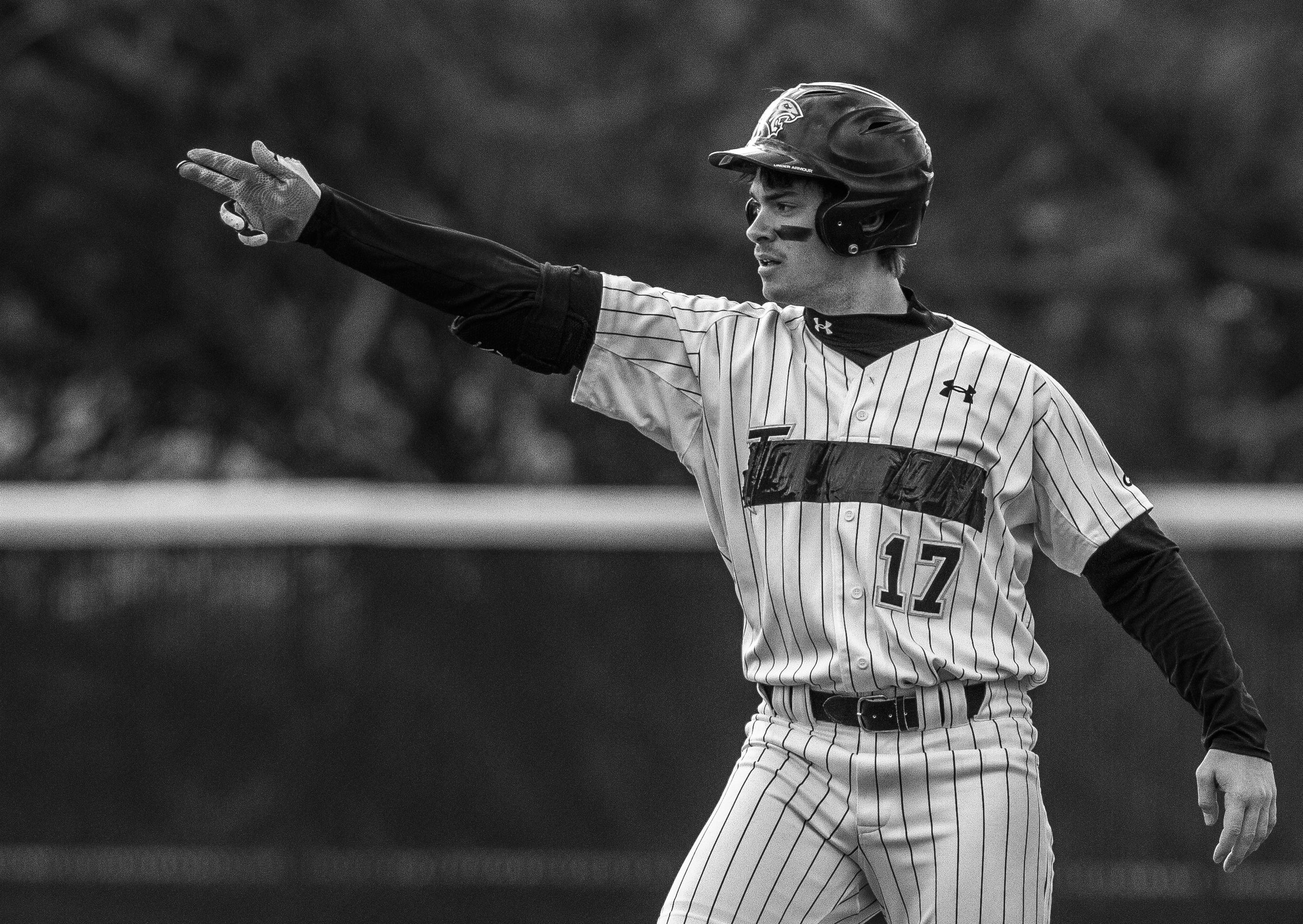 """Towson University outfielder Kurt Wertz signals to his team during their first home game on March 8, 2013 after receiving news that they will not have a 2014 season in Baltimore, Md. The entire team covered """"Towson"""" on their jerseys in protest of the recent decision."""