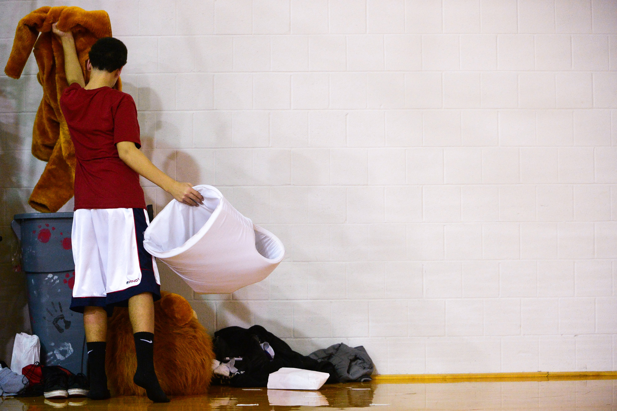The Dulaney High School Lion removes his costume during their game at Goucher College on Dec. 18, 2013.