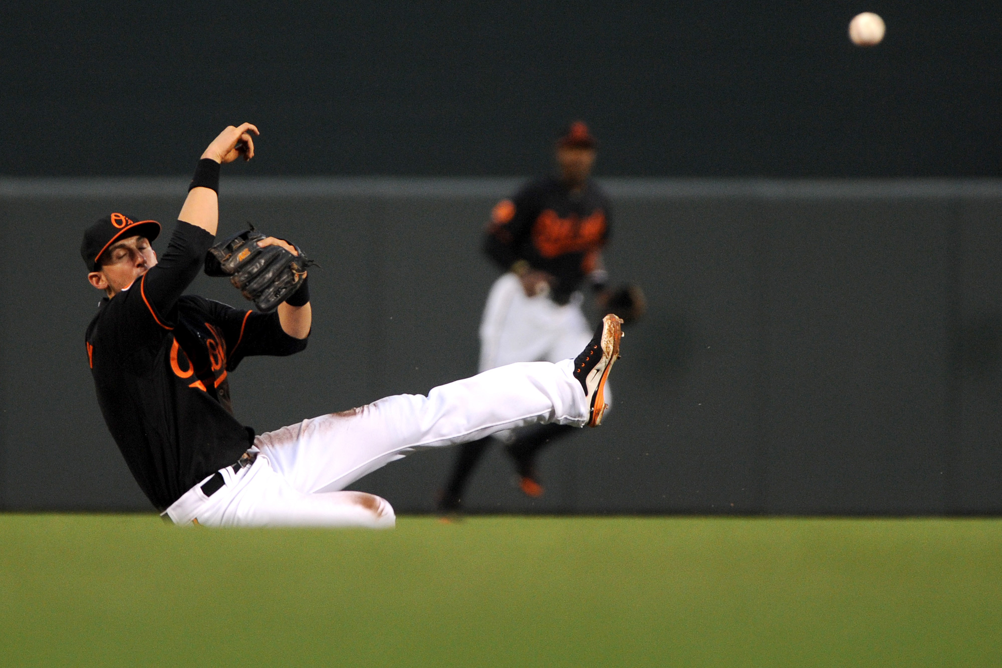 Baltimore Orioles second baseman Ryan Flaherty falls to the dirt after making a throw to first on June 30, 2013 at Oriole Park at Camden Yards in Baltimore, Md.