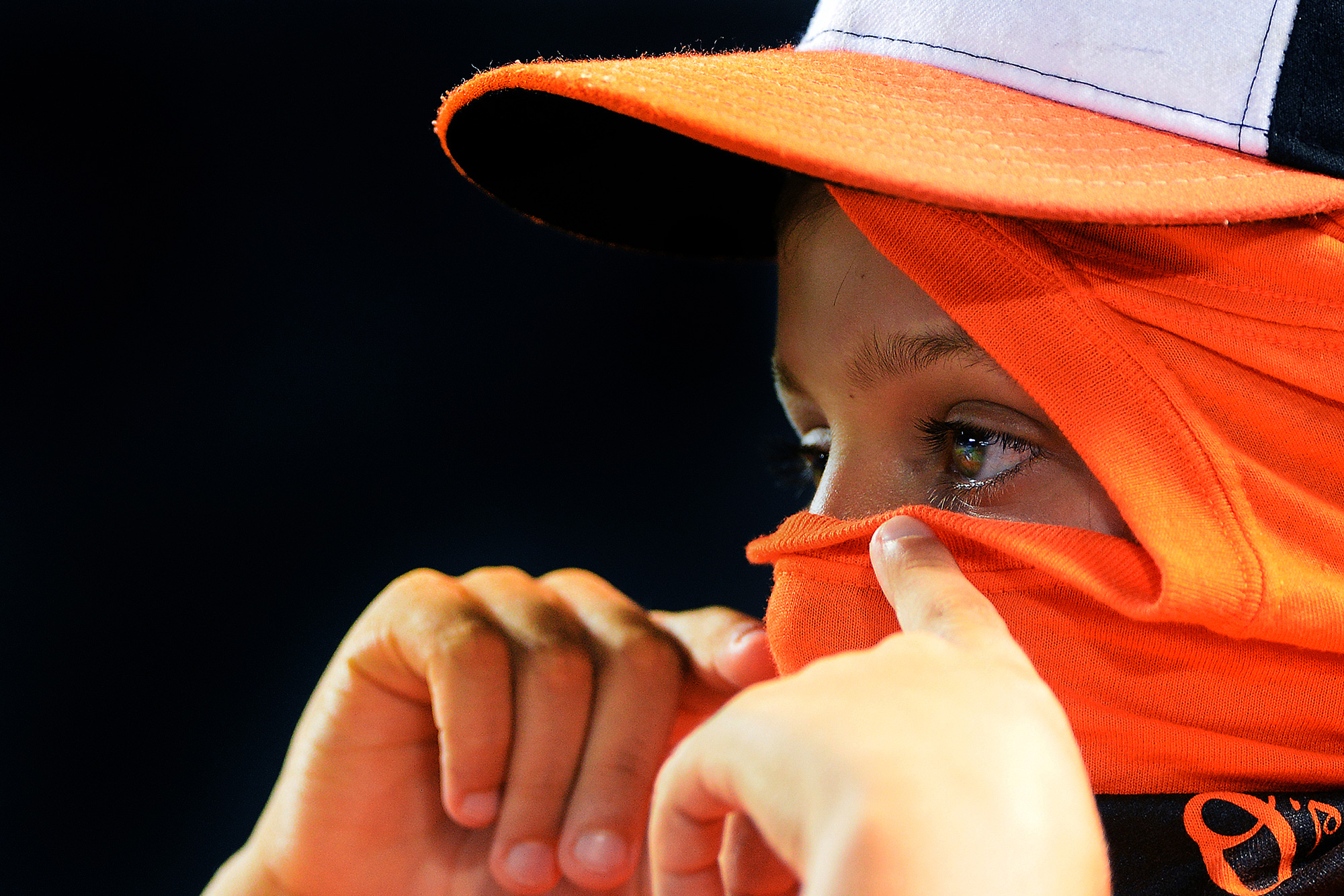 A fan creates a ninja mask out of a free giveaway shirt during a Baltimore Orioles home game on July 9, 2013 at Oriole Park at Camden Yards in Baltimore, Md.