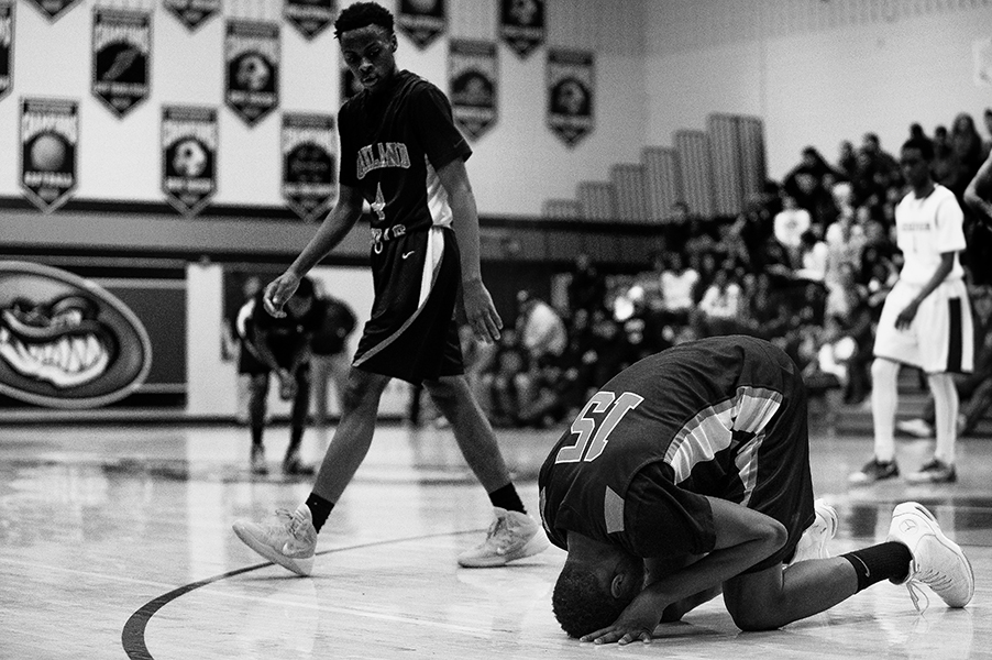 Forward Mamadou Ndiaye, bottom right, of Oakland Mills High School drops to the court in a combination of frustration and pain during a game against Reservoir High School on Jan. 25, 2014.