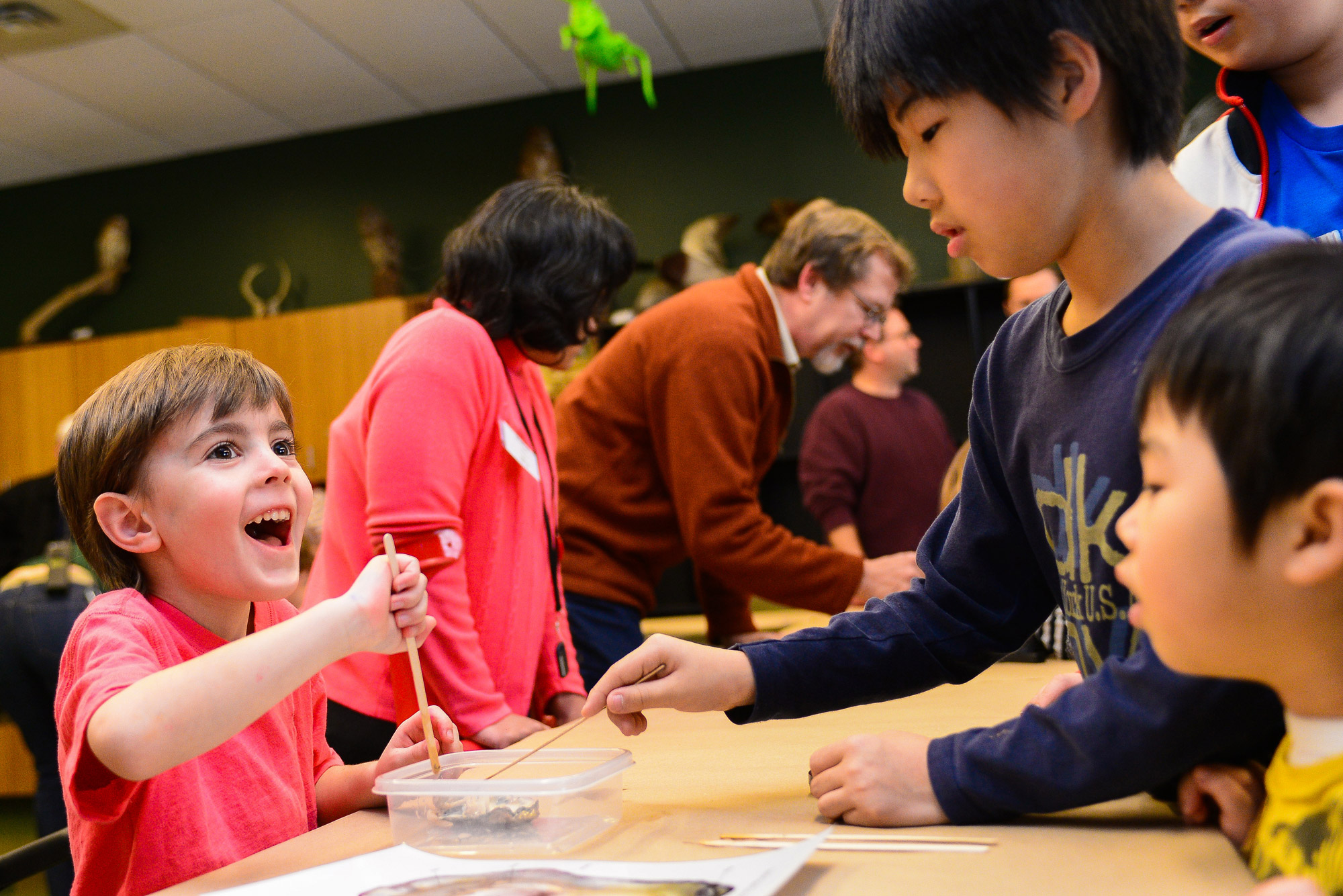 Dyson Kuhns, left, 6, of Owen Brown smiles while dissecting an oyster with Yuto Kawabata, 9, and his brother Yuki, right, 5 of Ellicott City.