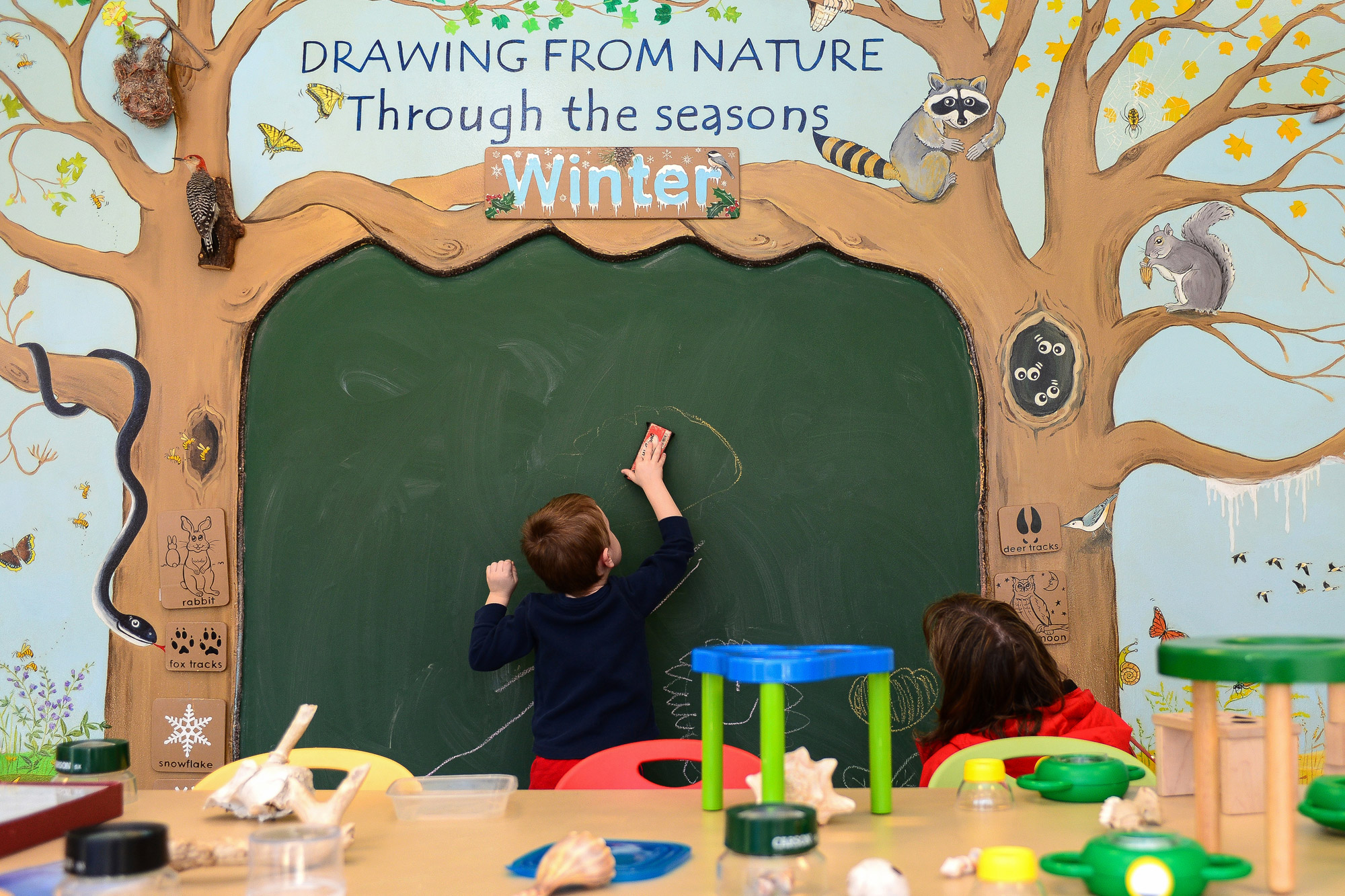 Adam Snyder, left, 4, of Cedar Acres draws on a chalkboard with his mother Leah.