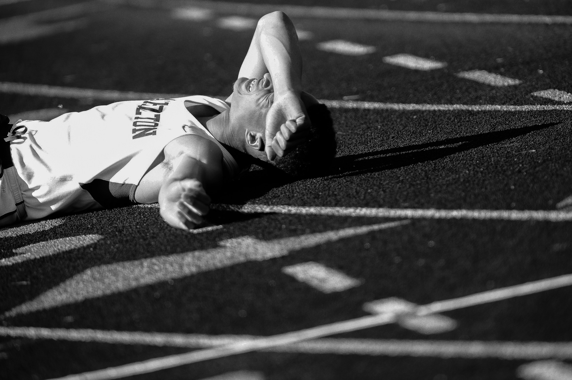 Miles Walker of Atholton High School rests on the track after the boy's 400 meter dash on the second day of the Howard County Track Championships at Wilde Lake High School in Columbia, Maryland on May 6, 2014.
