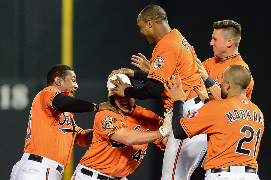 Steve Clevenger of the Baltimore Orioles is swarmed by his teammates after hitting a single RBI to win the game against the Houston Astros on May 10, 2014 at Oriole Park at Camden Yards in Baltimore, Maryland.