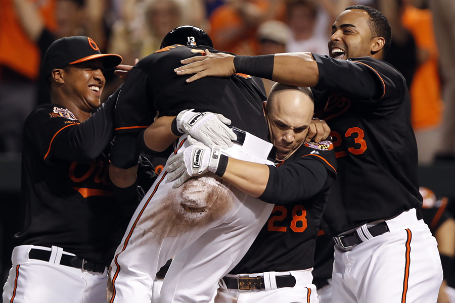 Steve Pearce, second from right, of the Baltimore Orioles lifts teammate Manny Machado into the air after he scores the winning run off of a single-RBI from Nick Hundley (not pictured) in the 10th inning of a MLB game against the New York Yankees on July 9, 2014 at Oriole Park at Camden Yards in Baltimore, Maryland.
