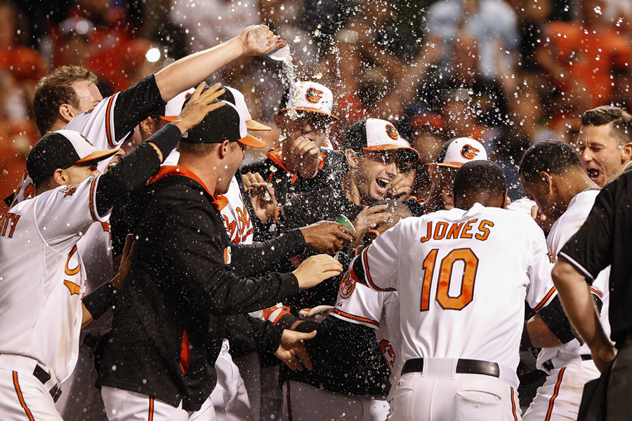 Members of the Baltimore Orioles celebrate after Manny Machado hits a walk-off during the 11th inning of a MLB game against the Los Angeles Anaheim Angels at Oriole Park at Camden Yards in Baltimore, Maryland on July 29, 2014.
