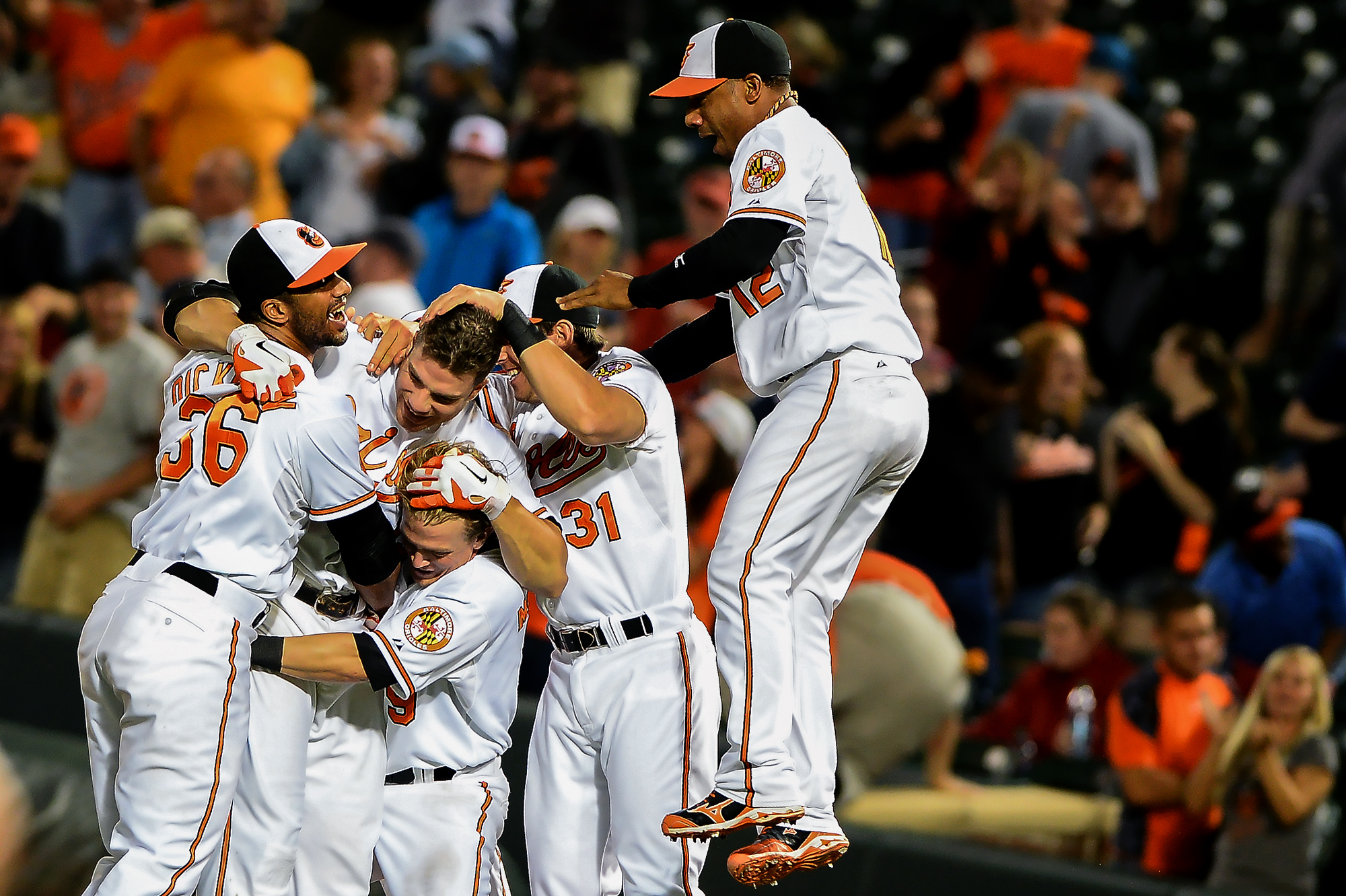 Chris Davis of the Baltimore Orioles is mobbed by his teammates after hitting the game winning RBIin the 13th inning against the Boston Red Sox at Oriole Park at Camden Yards on June 13, 2013 in Baltimore, Md.