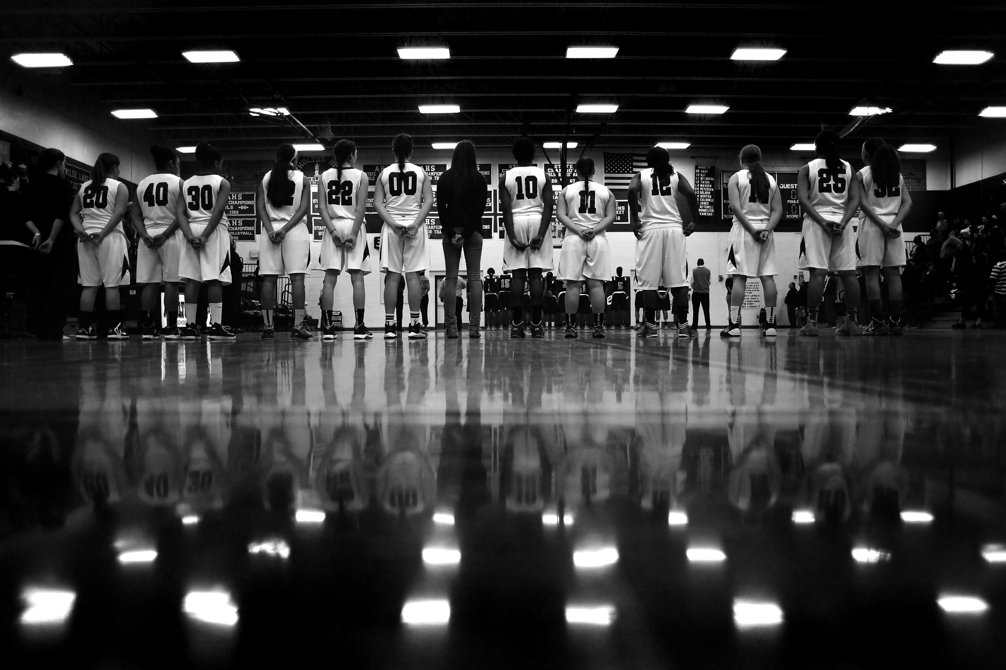 Atholton High School girl's basketball lines up for the national anthem before the start of the regional finals game in Columbia, Maryland on March 8, 2014.