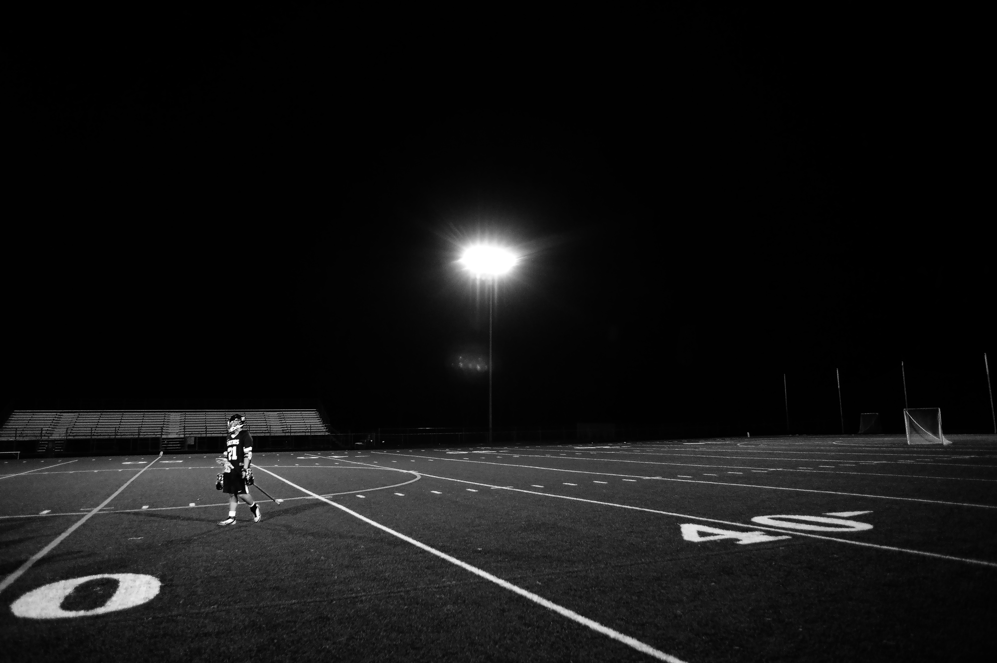 Jonathan Koh of Reservoir High School walks off the field after losing to Howard High School in a boy's lacrosse game in Columbia, Maryland on March 28, 2014.