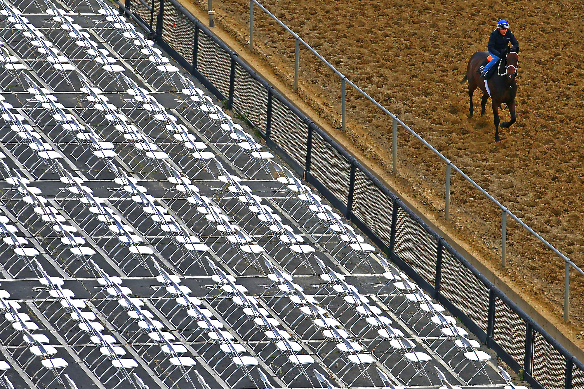 A horse and jockey walk the track one day prior to the 140th Preakness Stakes at Pimlico Race Course on May 15, 2015 in Baltimore, Maryland.
