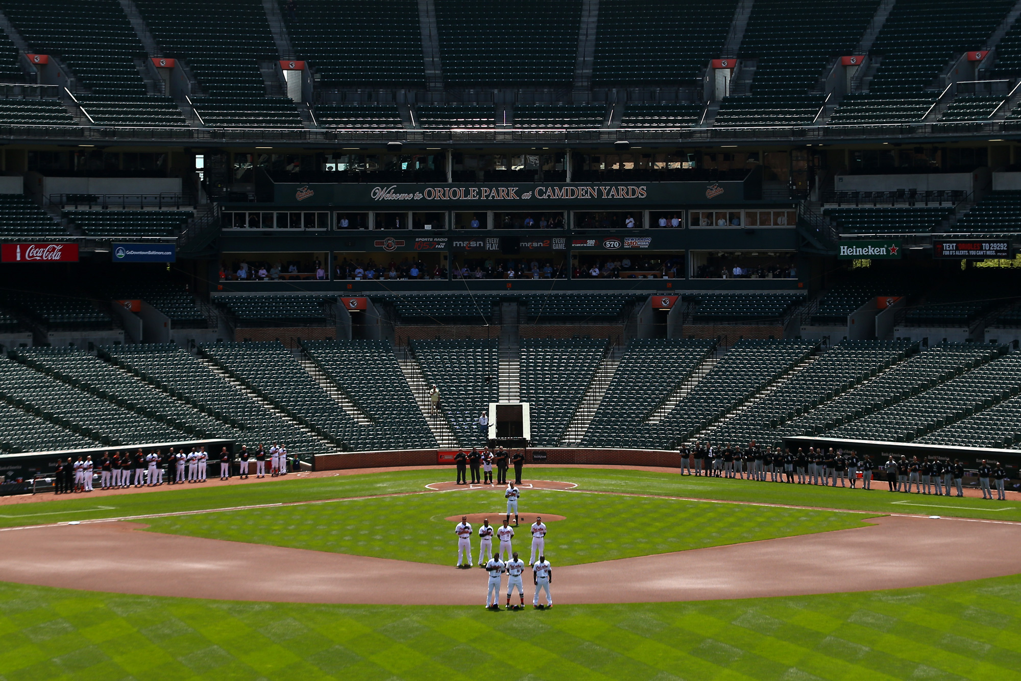 The Baltimore Orioles and Chicago White Sox stand for the nation anthem at an empty Oriole Park at Camden Yards on April 29, 2015 in Baltimore, Maryland.