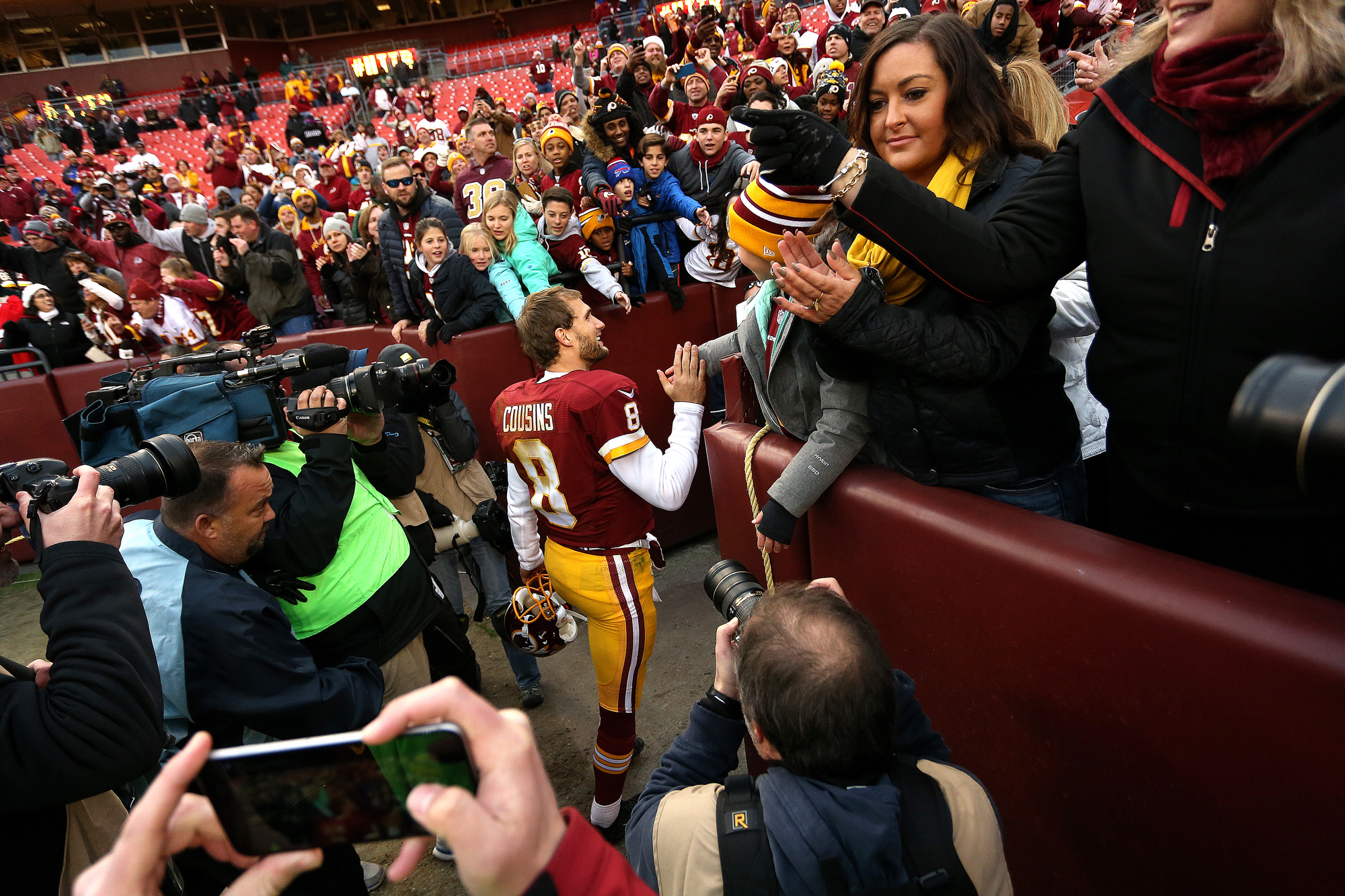 Quarterback Kirk Cousins #8 of the Washington Redskins celebrates with fans after the Washington Redskins defeated the Buffalo Bills 35-25 at FedExField on December 20, 2015 in Landover, Maryland.