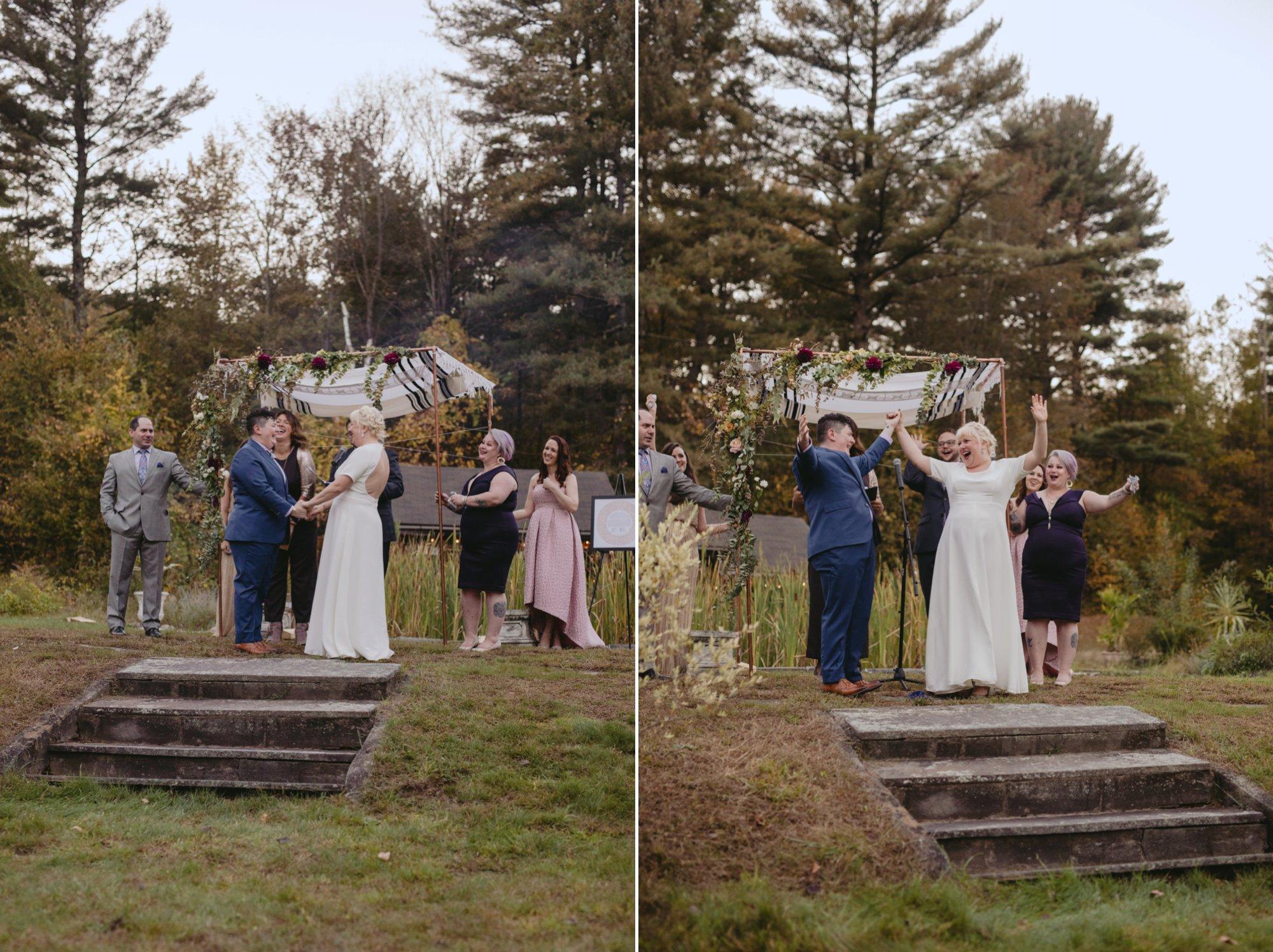 October Jewish lesbian wedding at Foxfire Mountain House in Upstate New York. Brides celebrating under chuppah.
