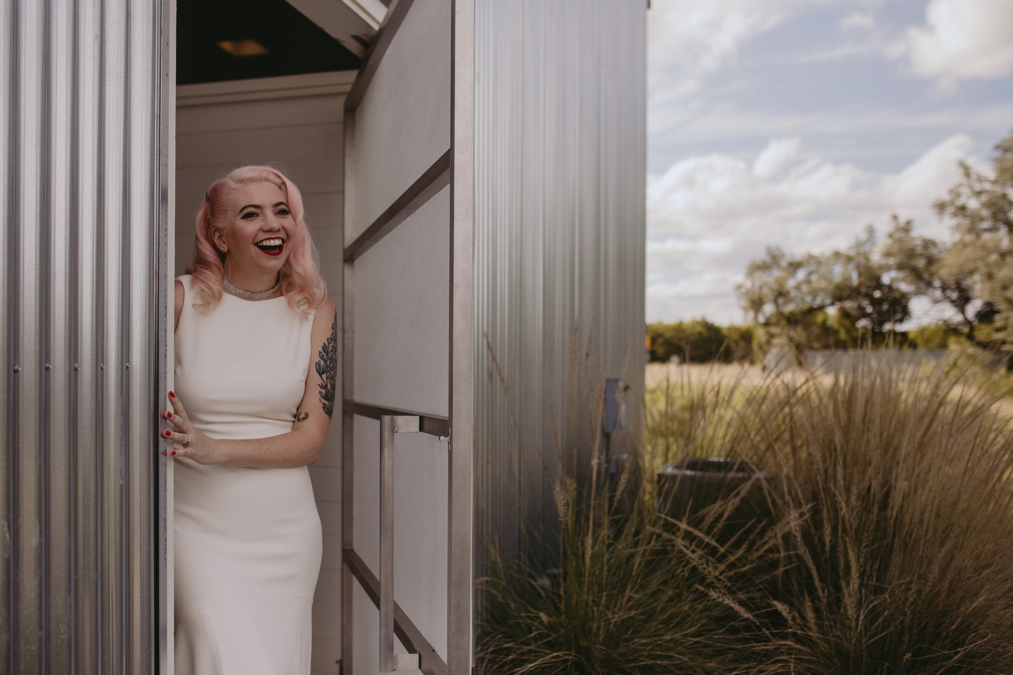 Bride with pink hair and groom in a purple suit prospect house wedding in austin tx with pastel decor and wild florals bride first look
