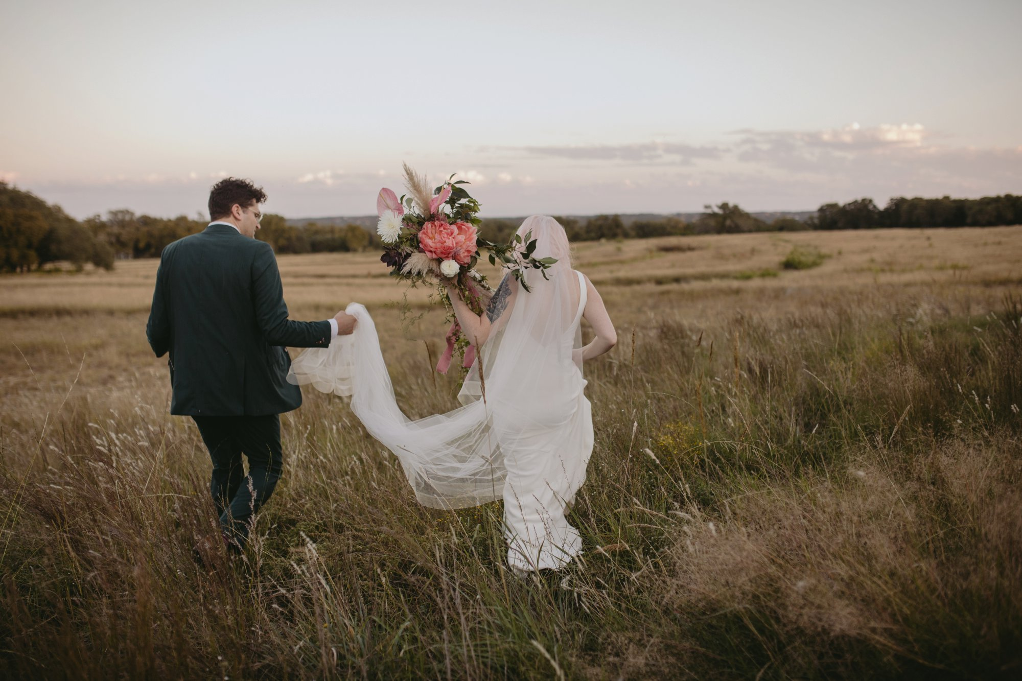 Bride with pink hair and groom in a purple suit prospect house wedding in austin tx with pastel decor and wild florals meadow