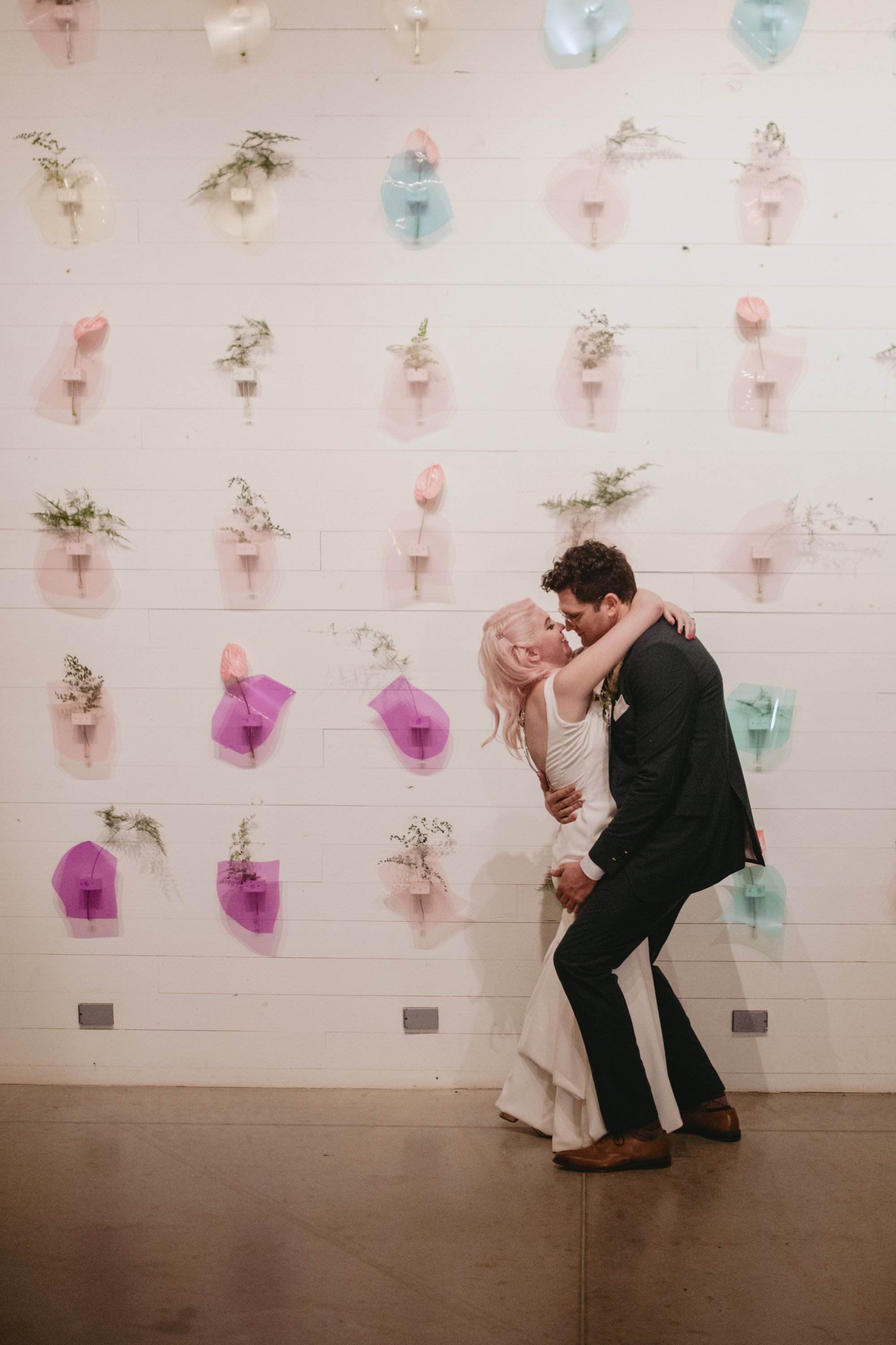 Bride with pink hair and groom in a purple suit prospect house wedding in austin tx with pastel decor and wild florals flower wall kiss