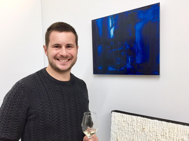 L'artiste Louis-Bernard St-Jean, devant l'une de ses nouvelles œuvres sur aluminium, avec un verre de vin à la main