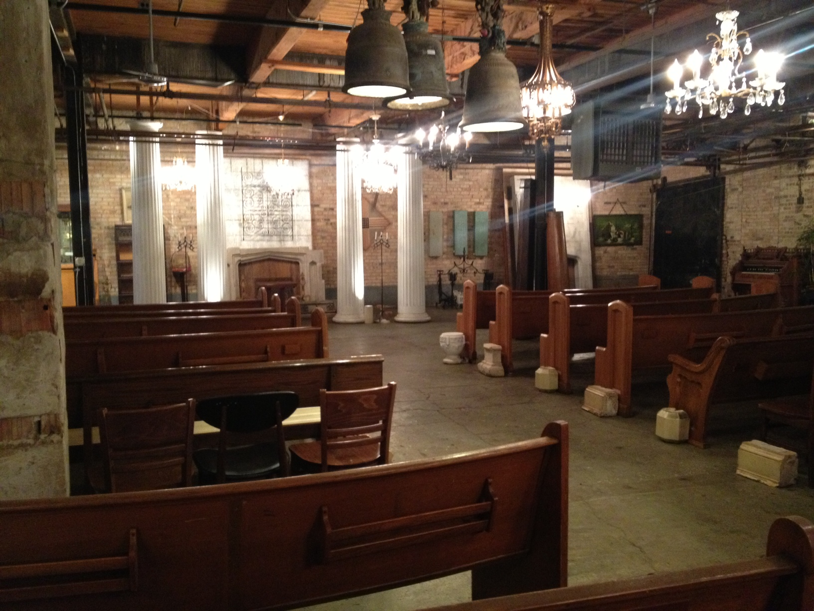 One of the potential wedding ceremony spaces in the building has super vintage pews and amazing chandeliers!