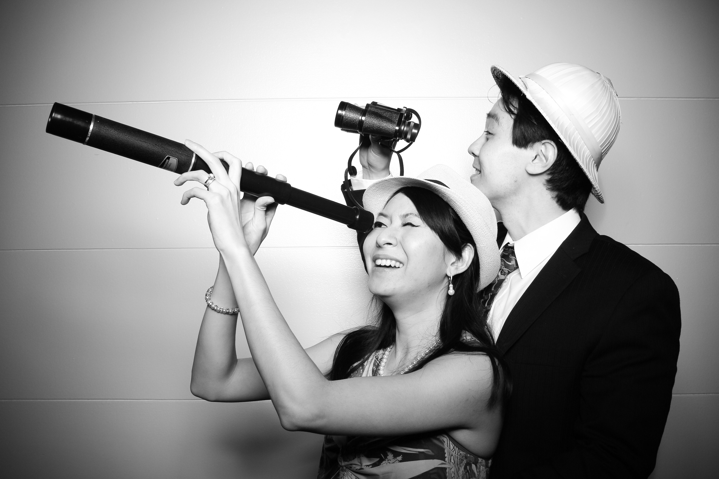 A photo booth picture of husband and wife posing in Stanley Field Hall with binoculars and telescope props!