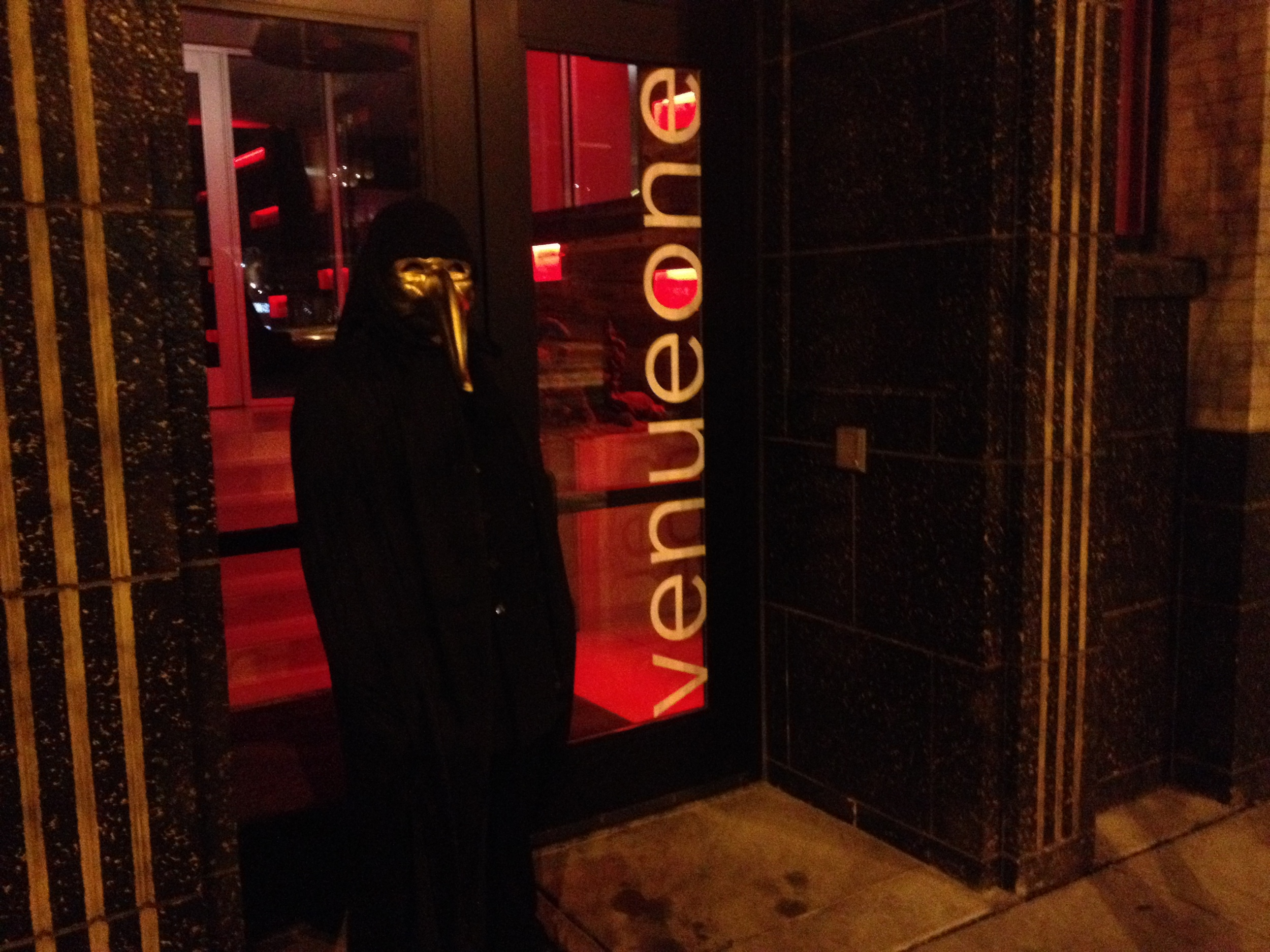 A picture of the entrance to Venue One with masked individual. The password please?