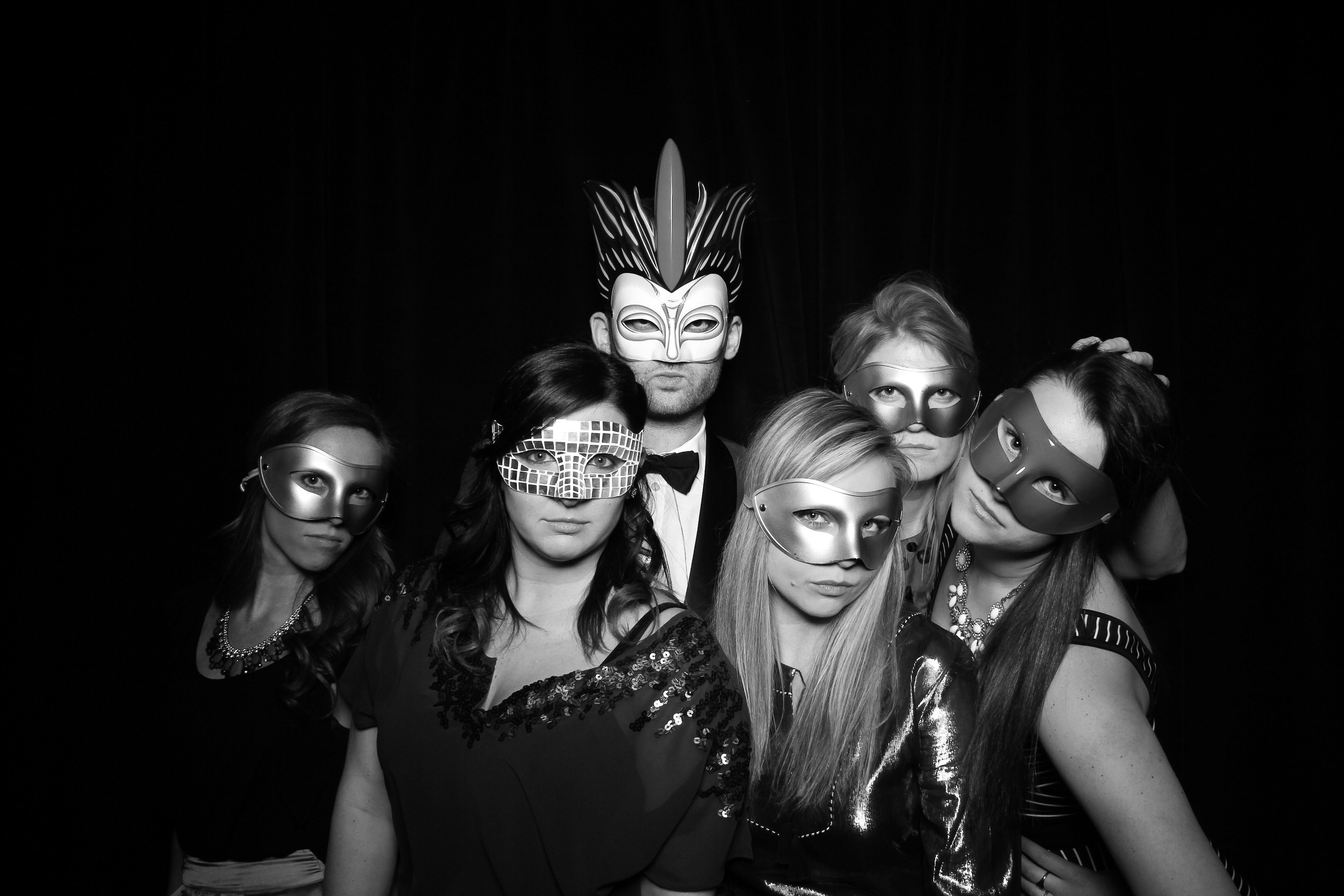 A group masquerade photo booth shot with the black draped velvet at Venue One.