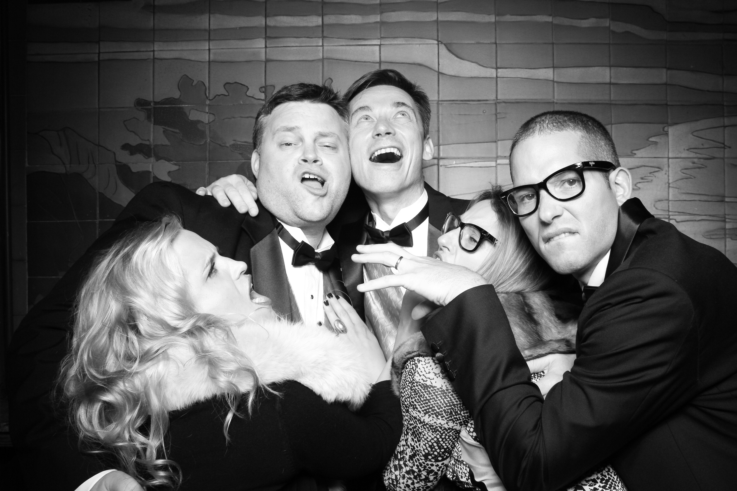 The two grooms pose for a silly picture with friends!