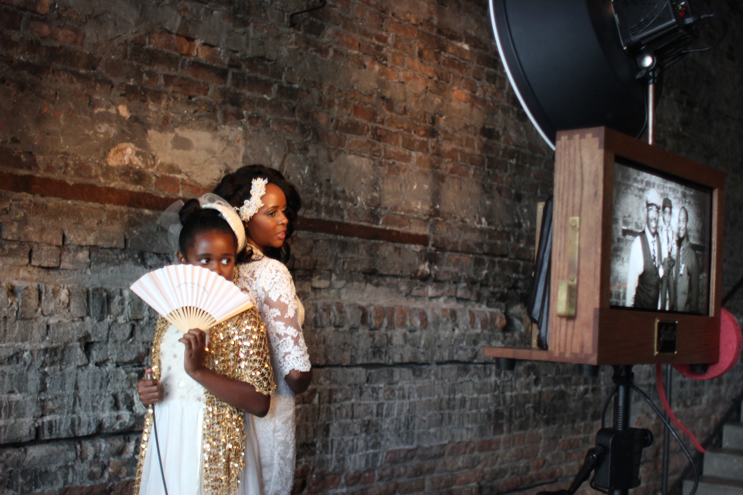 The bride having fun in the photo booth! We love the rustic look of the exposed brick at A New Leaf!