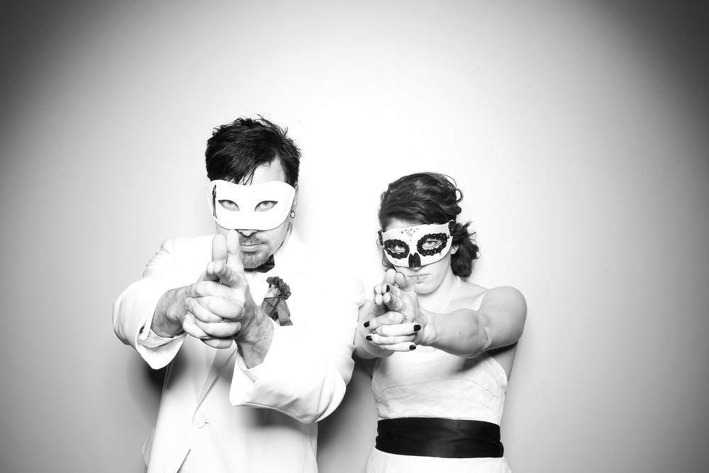 The bride and groom take a photo booth picture at their Masquerade inspired Halloween Wedding!